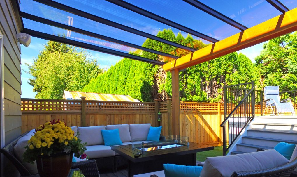 a warm backyard with a glass canopy on timber frame
